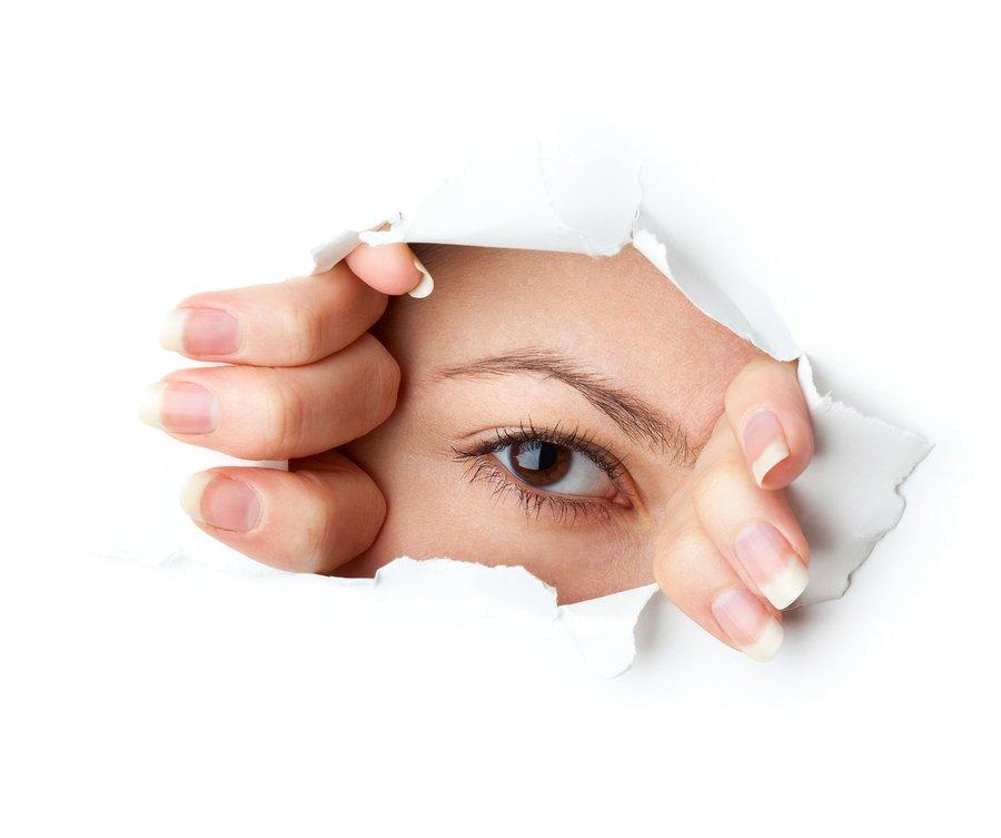 bigstock-Eye-looking-through-hole-Isol-26042978